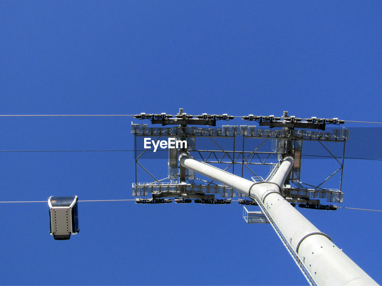 sky, blue, clear sky, low angle view, industry, metal, nature, copy space, architecture, built structure, day, technology, no people, factory, fuel and power generation, building exterior, tall - high, outdoors, sunlight, connection, power supply, directly below, industrial equipment