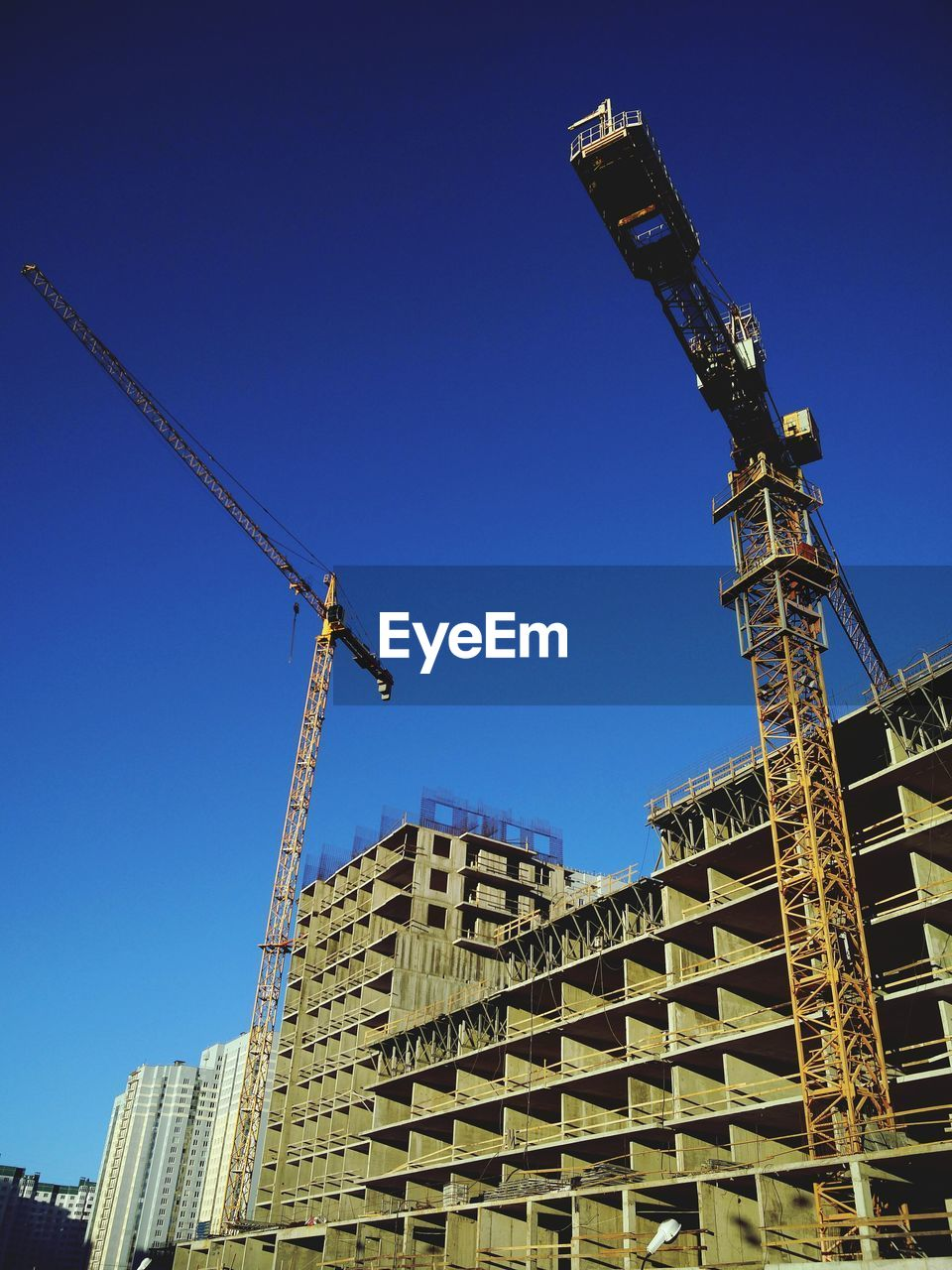 architecture, construction site, built structure, building exterior, development, construction, low angle view, blue, crane - construction machinery, progress, building - activity, clear sky, city, construction machinery, outdoors, day, crane, no people, skyscraper, industry, modern, sky