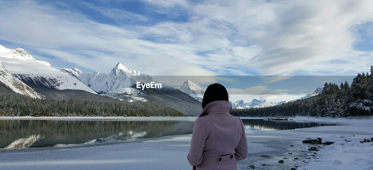 Rear View Of Woman Standing By Maligne Lake Against Cloudy Sky During Winter
