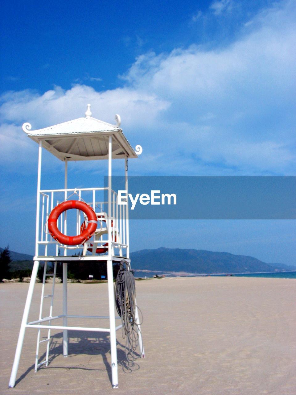 Lifeguard tower on sandy beach against sky