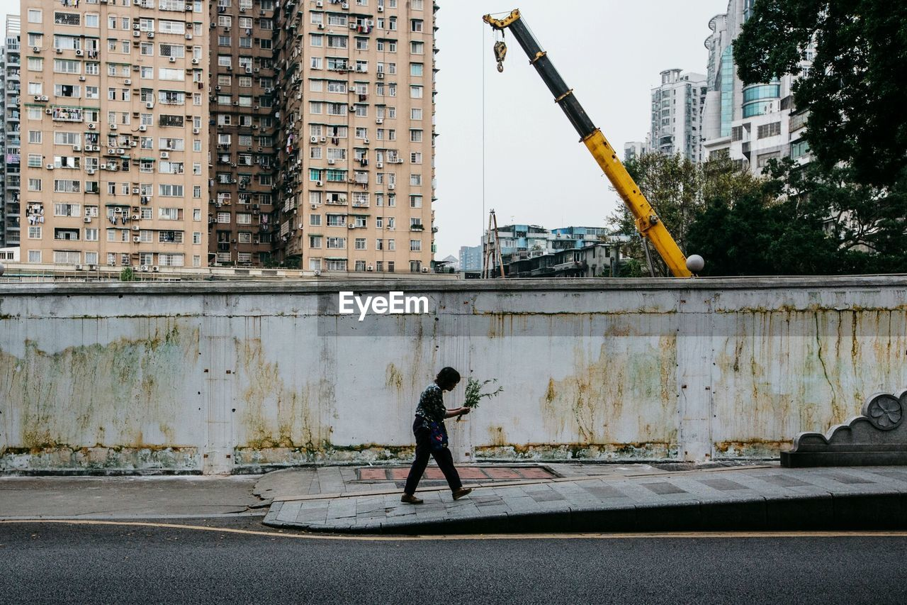 Side View Of Woman Walking On Sidewalk Against Wall In City