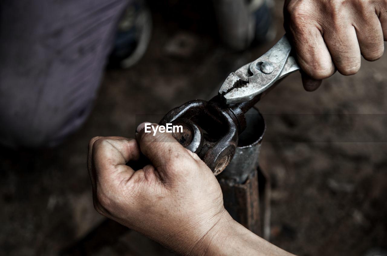 Close-Up Of Mechanics Working At Workshop