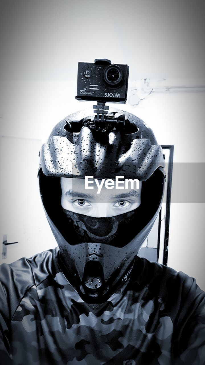 portrait, headshot, front view, indoors, one person, obscured face, looking at camera, helmet, disguise, headwear, mask, unrecognizable person, men, close-up, leisure activity, lifestyles, young men, clothing, wall - building feature