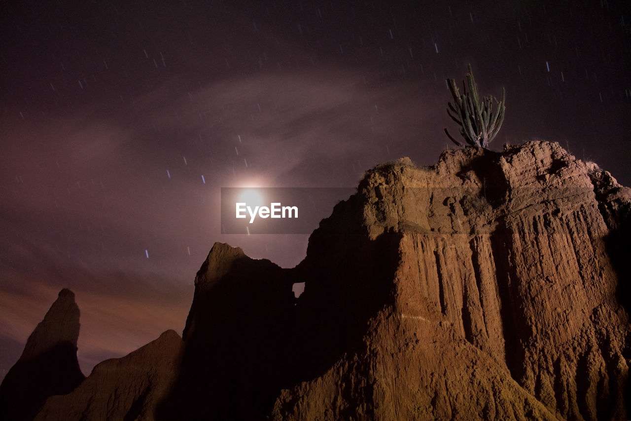sky, night, scenics - nature, beauty in nature, tranquil scene, star - space, space, rock, tranquility, rock formation, nature, low angle view, no people, mountain, moon, cloud - sky, physical geography, silhouette, rock - object, astronomy, moonlight, formation