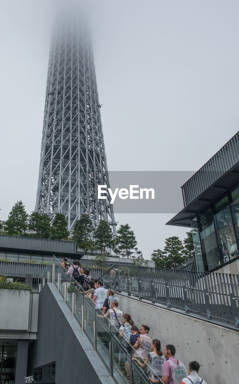 architecture, built structure, large group of people, building exterior, real people, tower, men, travel destinations, modern, skyscraper, women, tourism, city, leisure activity, clear sky, travel, day, low angle view, lifestyles, outdoors, sky, tree, people