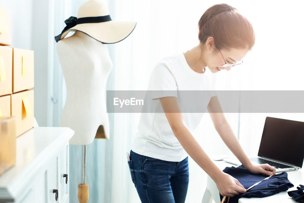 Smiling woman measuring textile at studio