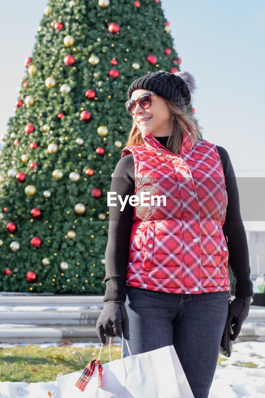 Woman standing against christmas tree during winter