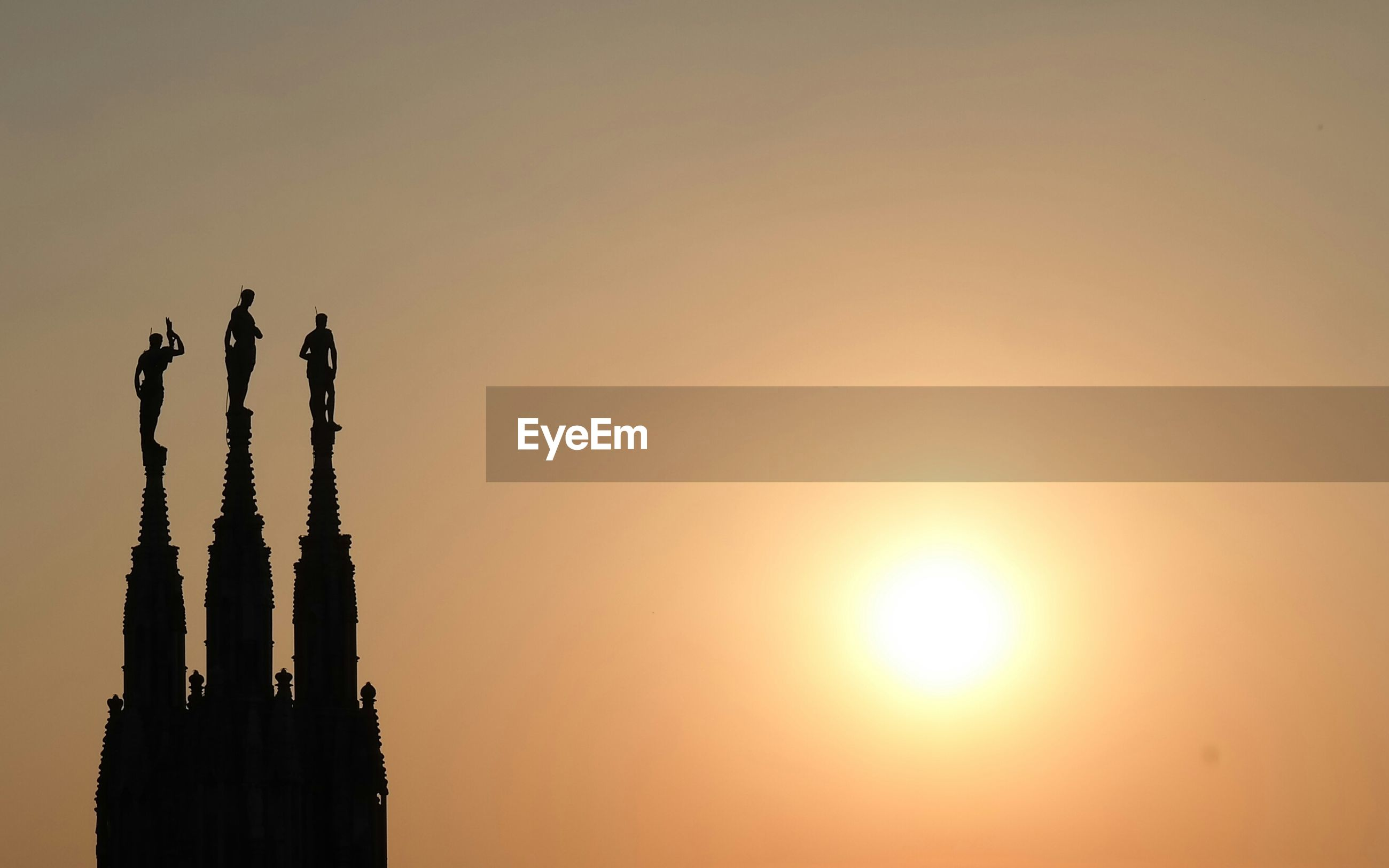 Silhouette spire of milan cathedral against orange sky during sunset