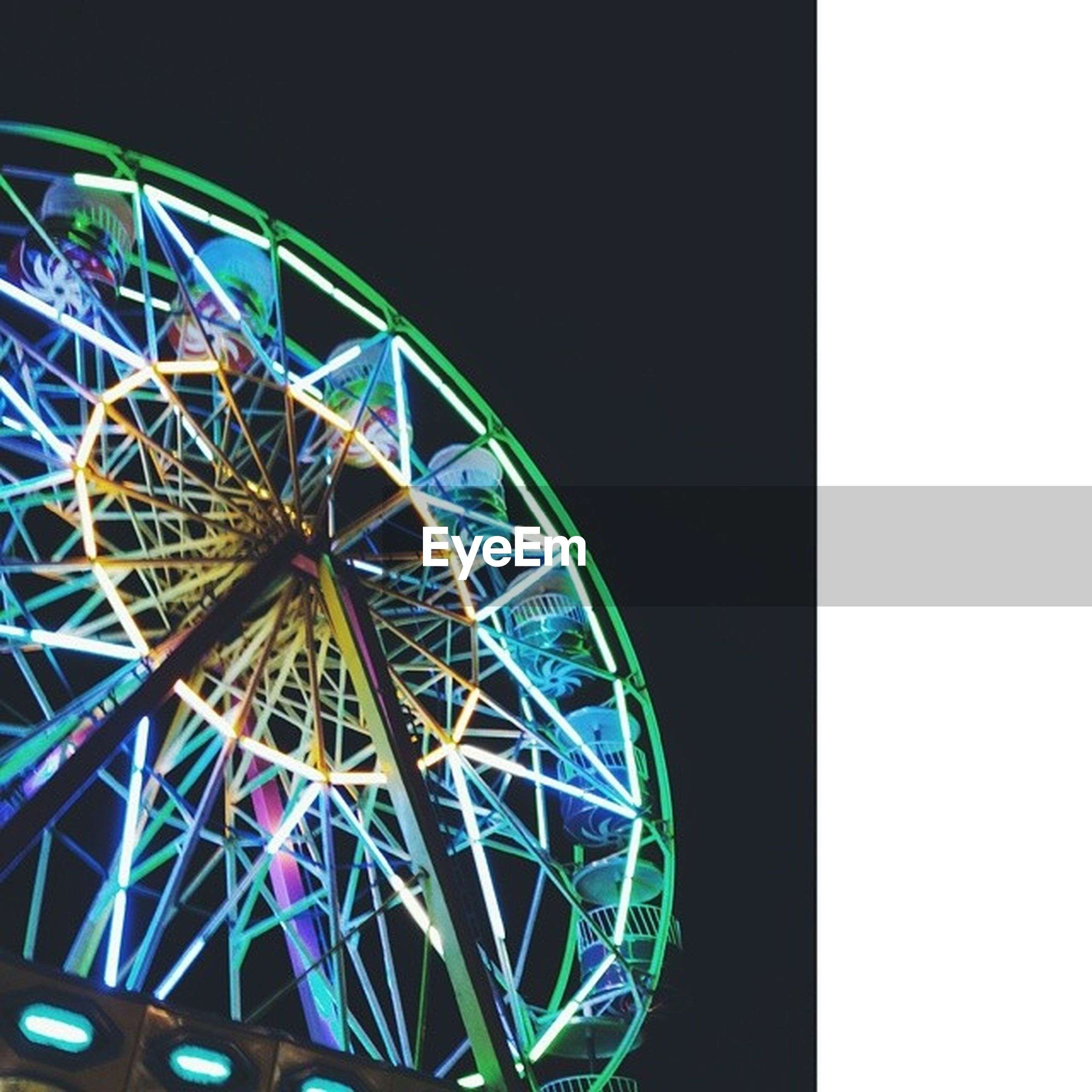 amusement park, ferris wheel, amusement park ride, arts culture and entertainment, clear sky, low angle view, illuminated, blue, copy space, circle, night, multi colored, built structure, fun, sky, architecture, outdoors, metal, no people, traveling carnival