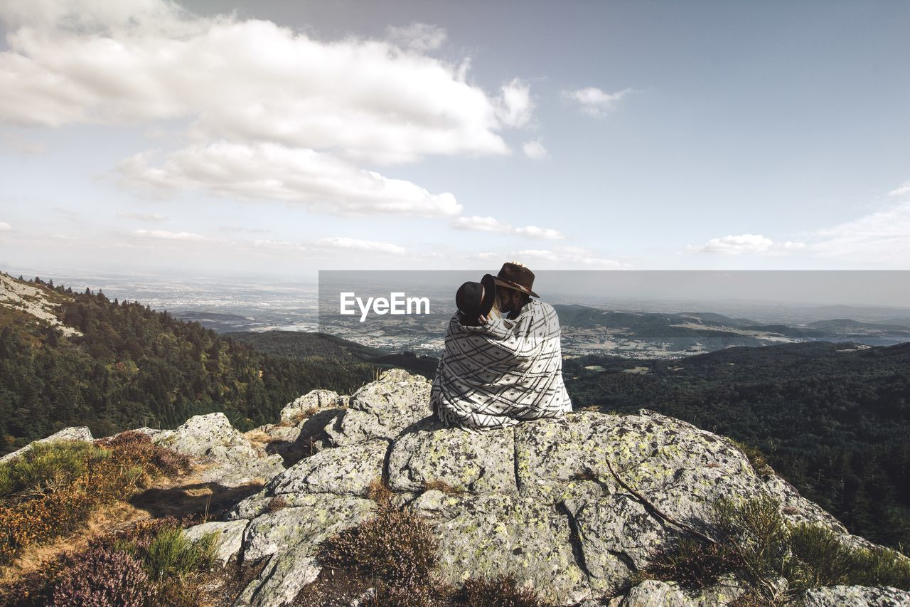 Rear View Of Couple Wearing Hats Kissing On Mountain Against Sky