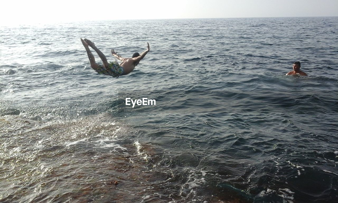 sea, real people, water, men, lifestyles, two people, enjoyment, leisure activity, horizon over water, swimming, nature, fun, day, weekend activities, jumping, shirtless, outdoors, full length, beauty in nature, togetherness, sky, adult, people