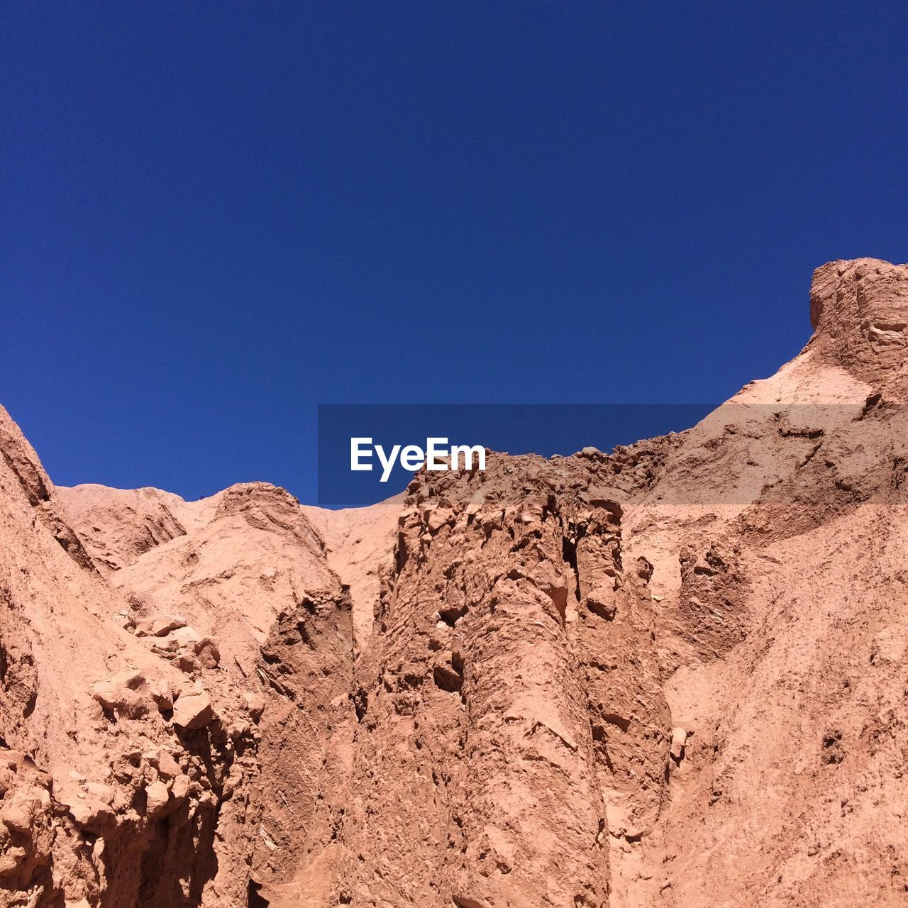 Low angle view of rocky wall against blue sky