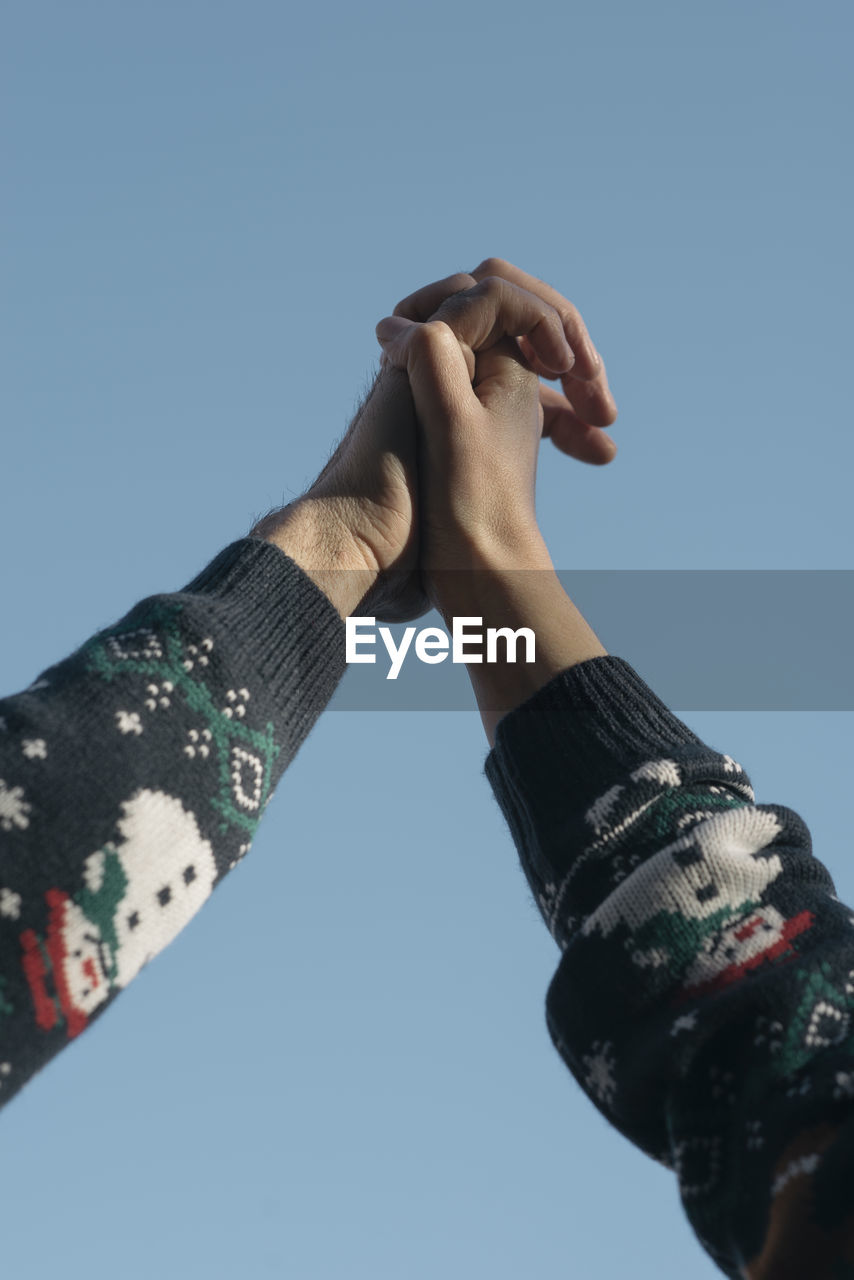 Low Angle View Of Couple Holding Hands Against Clear Sky