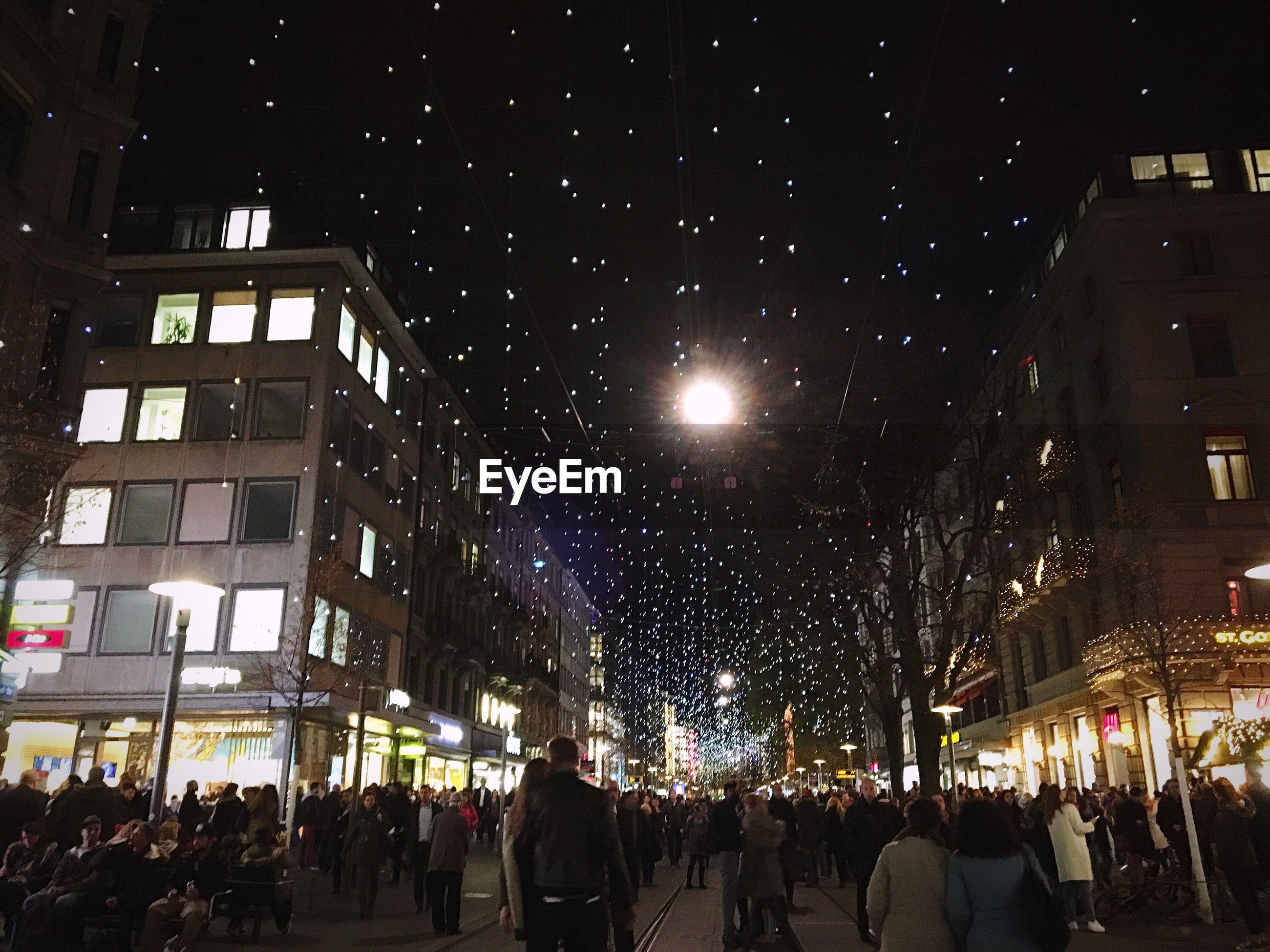 People on city street with illuminated christmas lights