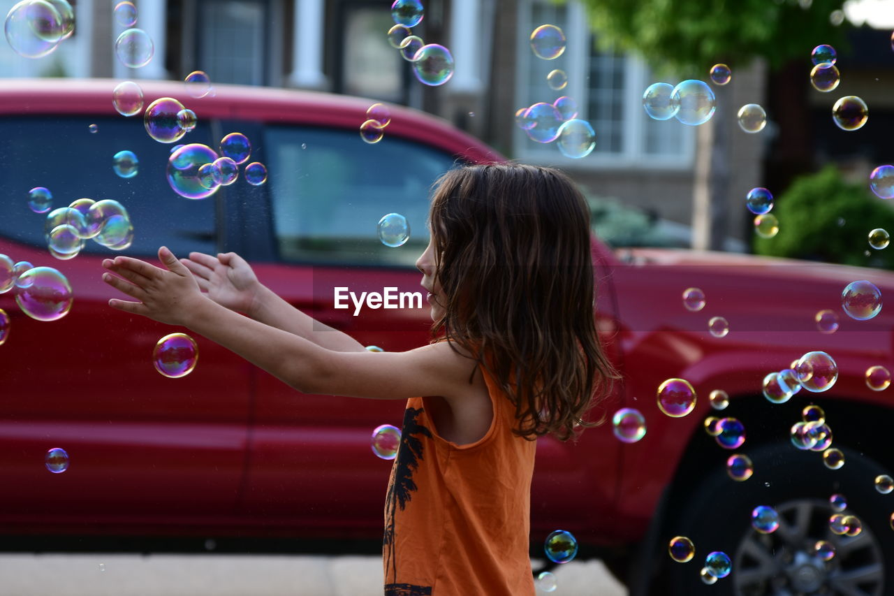 Side view of cute girl playing with bubbles at street