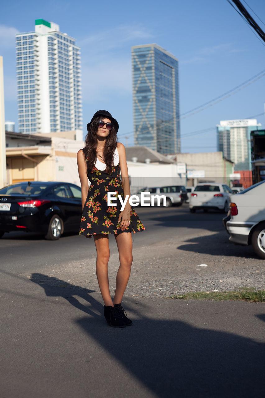 Full length of woman in city against sky
