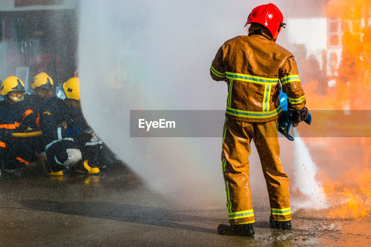 Rear View Of Firefighter Spraying Water On Fire While Standing At Street