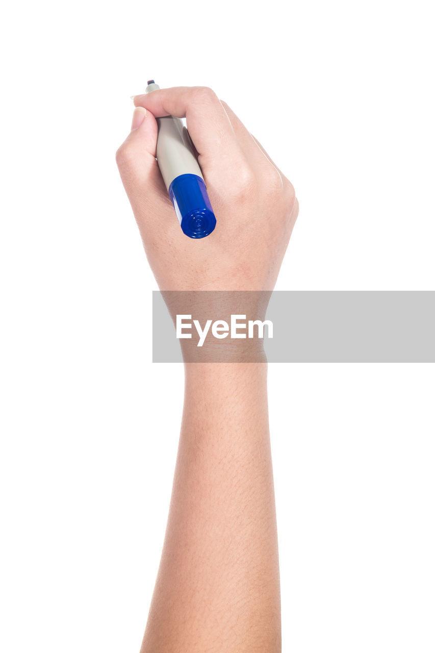 Cropped hand holding felt tip pens against white background