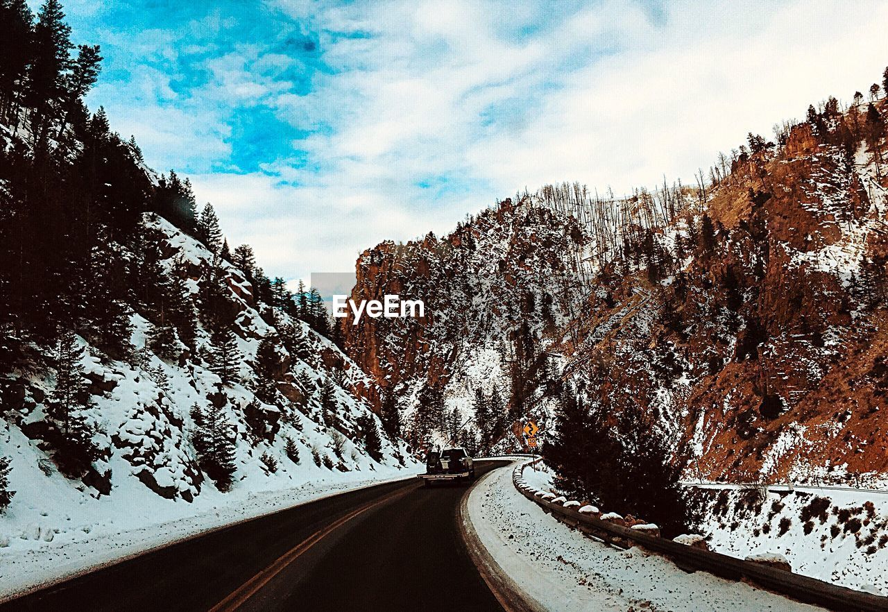 sky, snow, cloud - sky, winter, tree, cold temperature, transportation, road, nature, direction, the way forward, plant, scenics - nature, no people, mountain, beauty in nature, day, tranquil scene, non-urban scene, diminishing perspective, snowcapped mountain