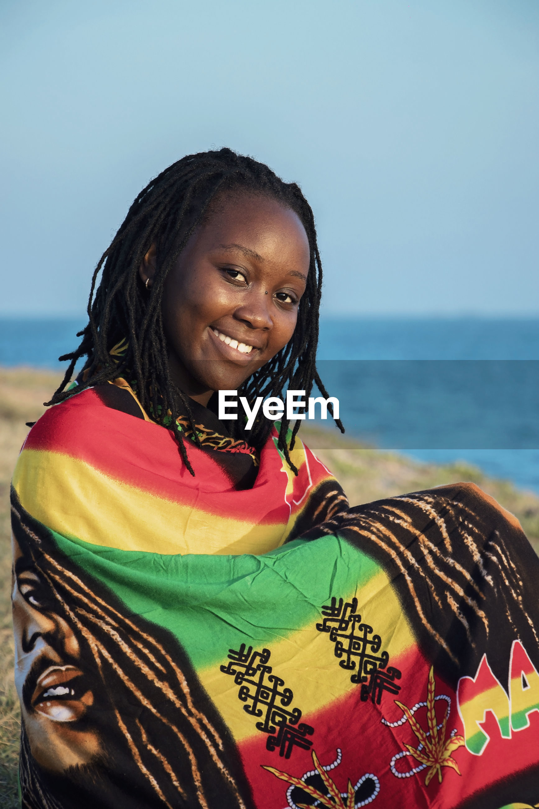 Portrait of smiling young woman wrapped in scarf standing at beach