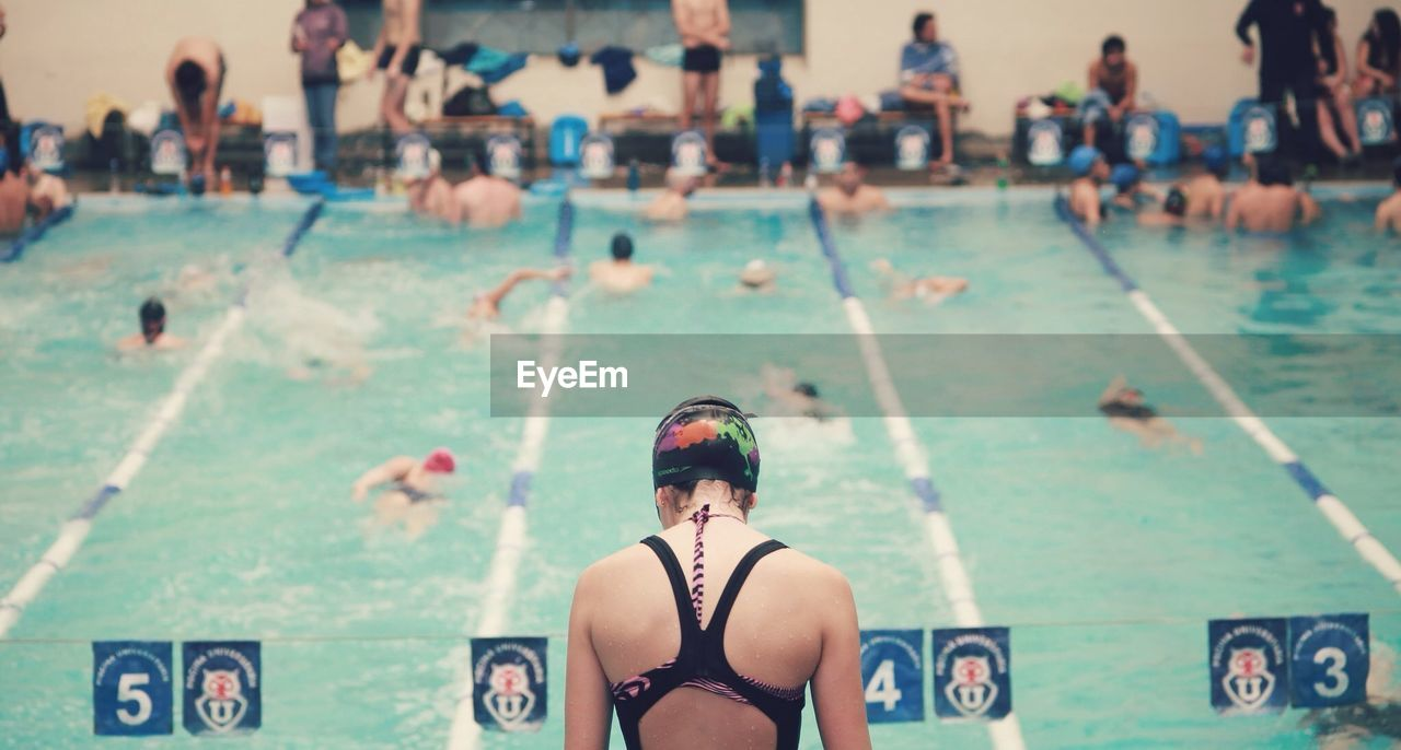 real people, incidental people, lifestyles, one person, leisure activity, swimming pool, focus on foreground, water, day, outdoors, looking at camera, young adult, people