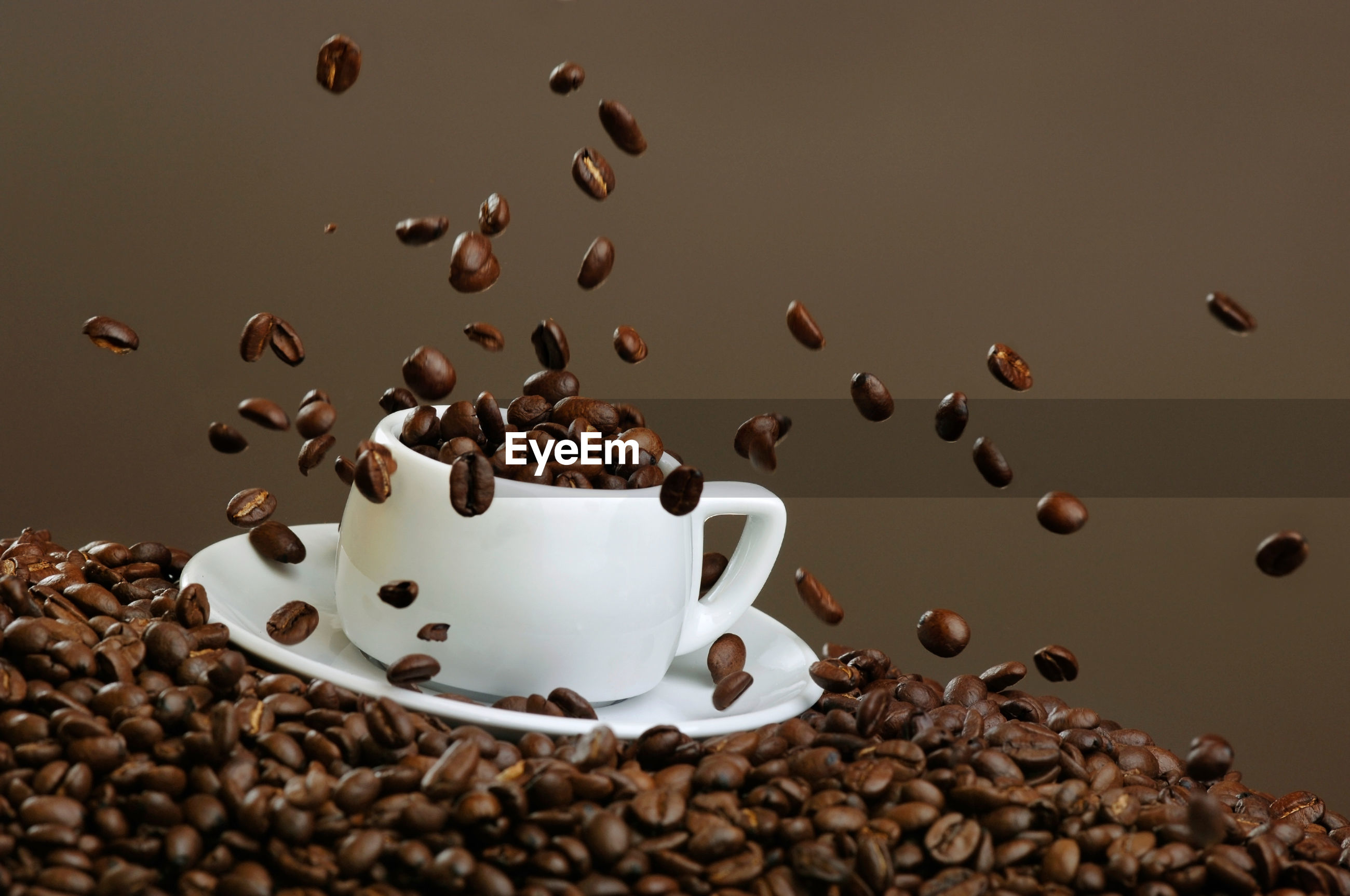 Roasted coffee beans splashing over cup and saucer