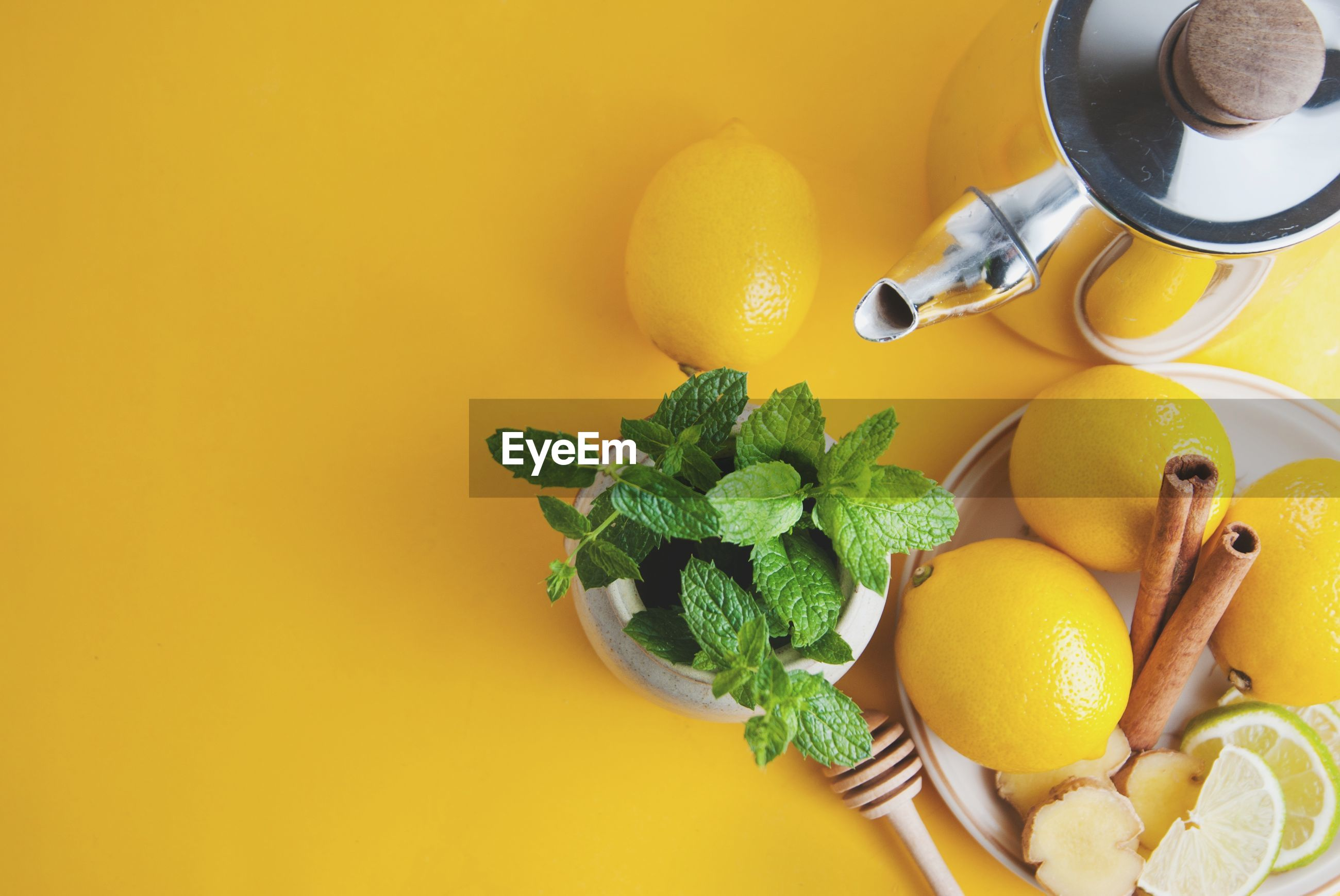 High angle view of ingredients with kettle over yellow background
