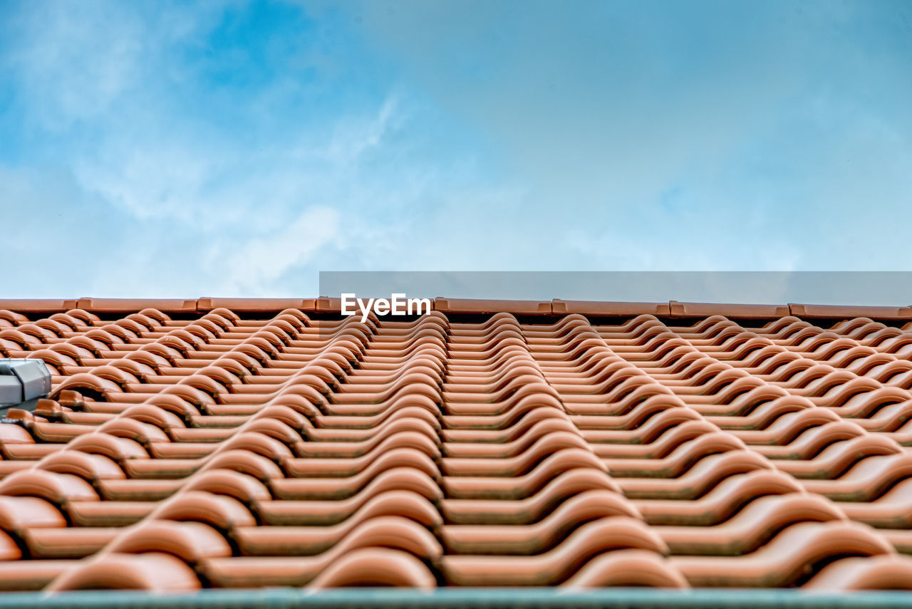 Low angle view of roof tiles against sky