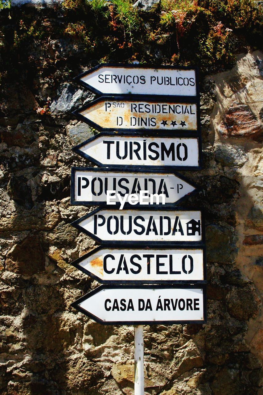 Close-up of metallic signs against stone wall