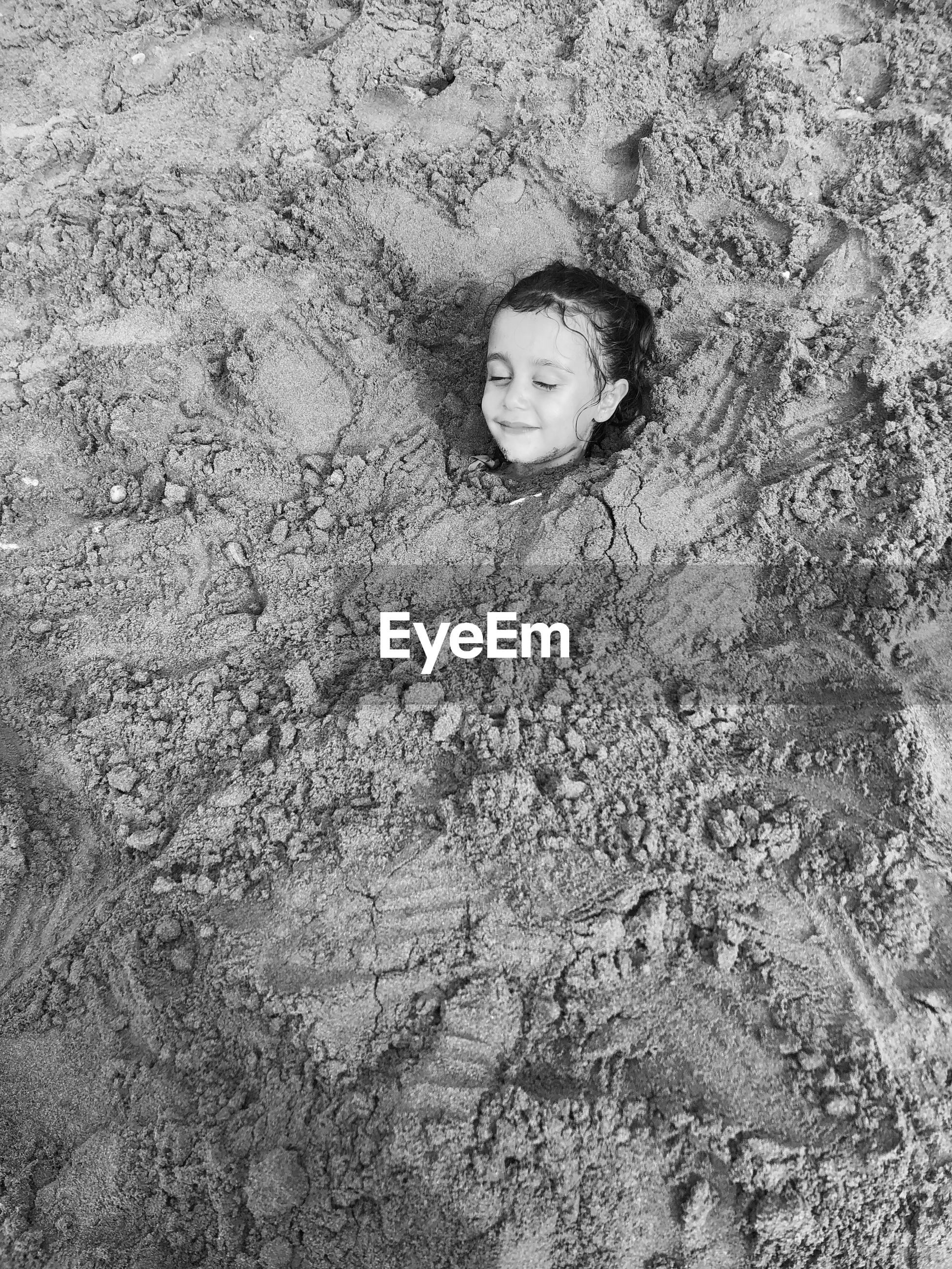 High angle view of smiling girl buried in sand