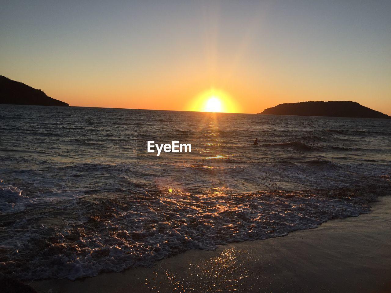 sunset, sky, water, beauty in nature, sea, scenics - nature, sun, tranquility, tranquil scene, land, beach, idyllic, nature, sunlight, horizon, no people, orange color, non-urban scene, wave, horizon over water, lens flare, outdoors