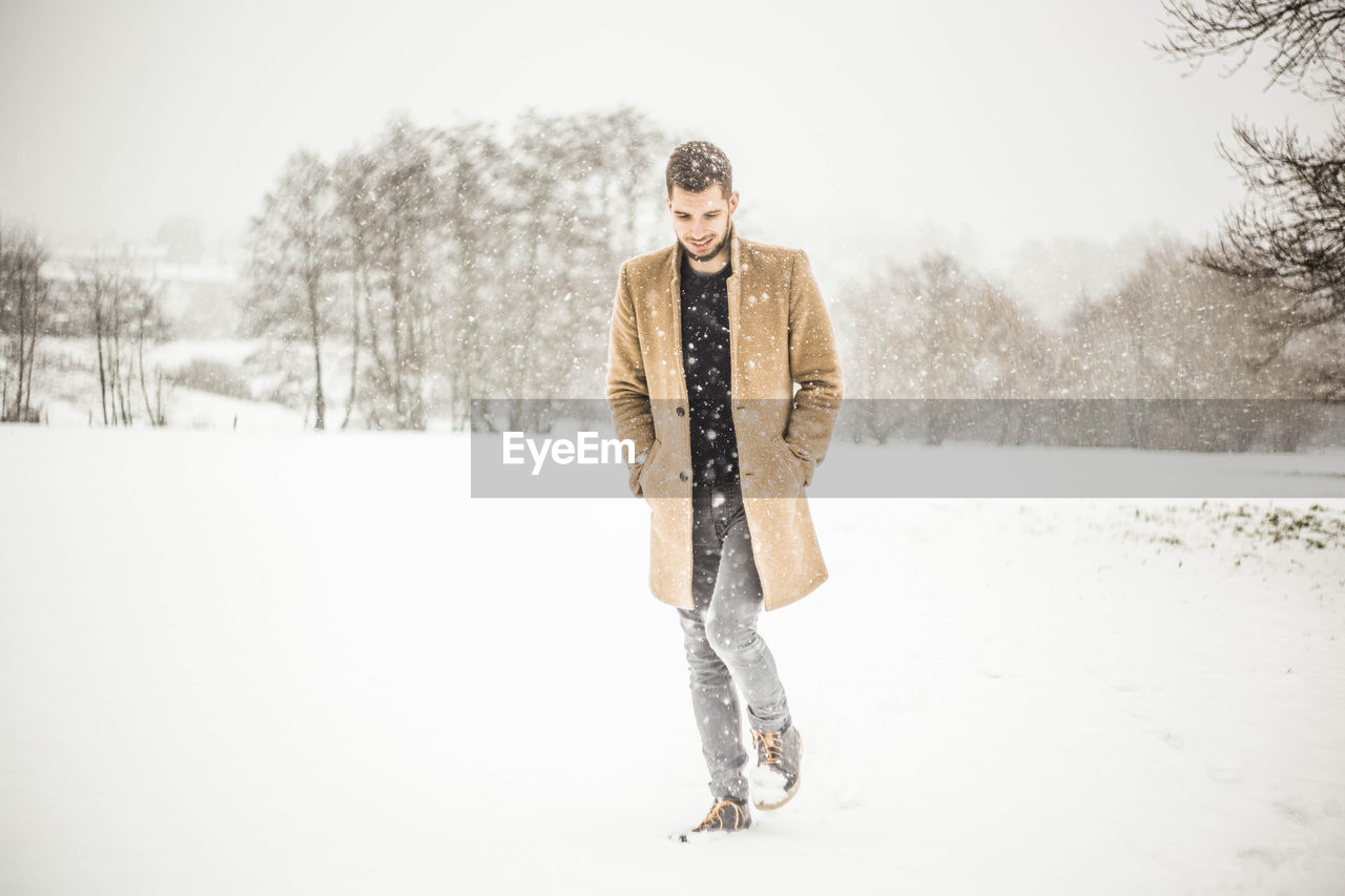 Young Man On Snow Covered Tree