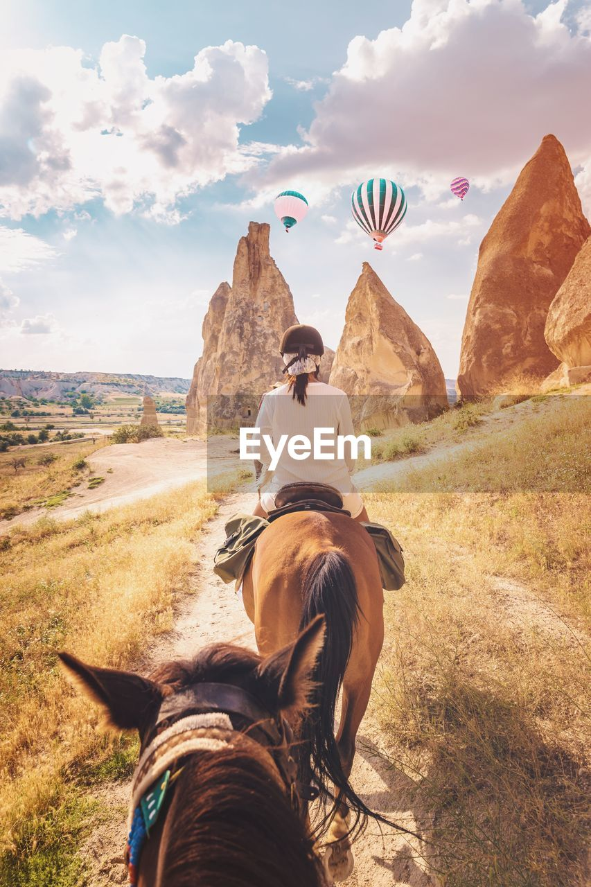 Rear view of woman riding horse against hot air balloons flying over landscape