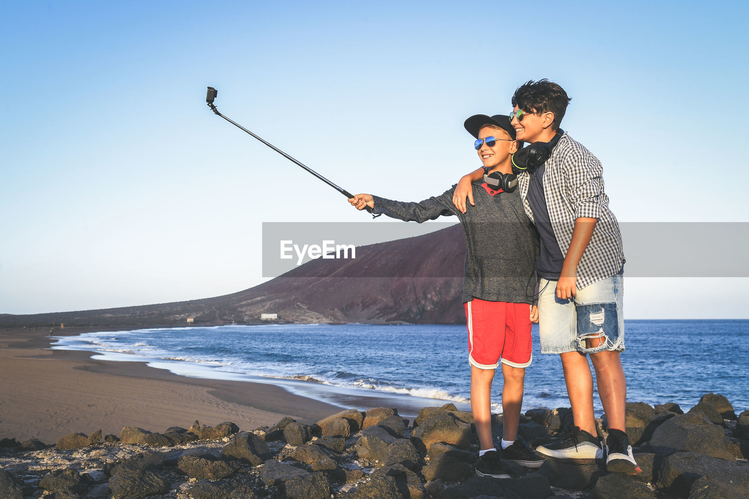 Brothers using mobile phone while standing at beach