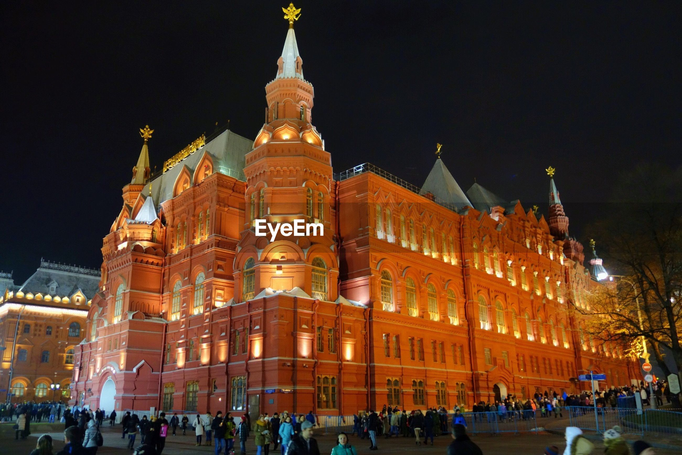 Crowd visiting illuminated historic building against clear sky at night