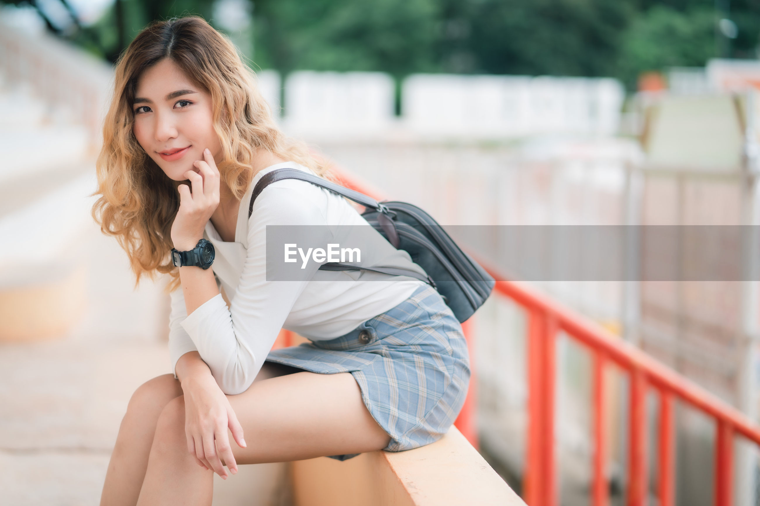 Portrait of beautiful young woman sitting by railing