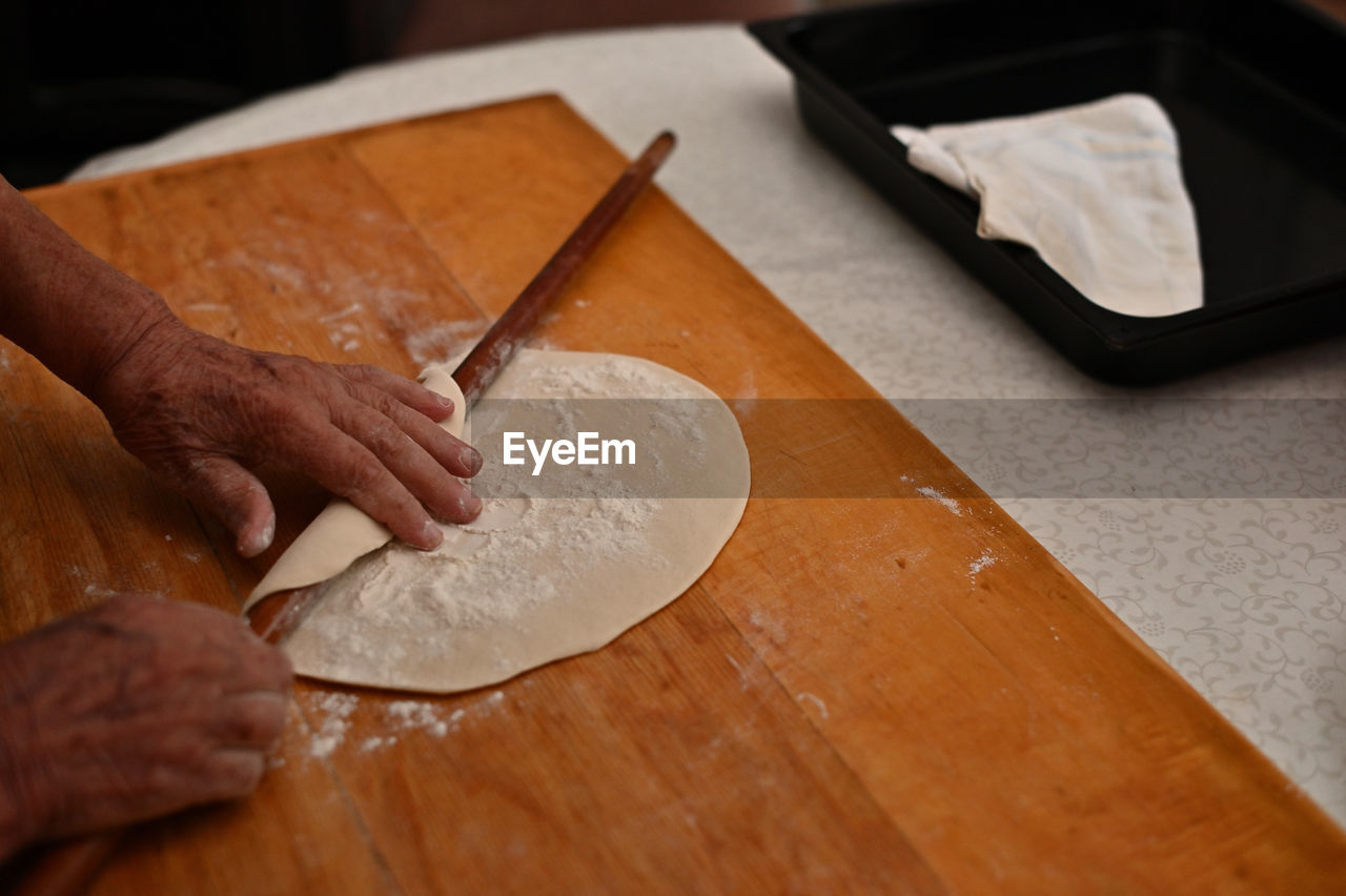 PERSON PREPARING FOOD ON TABLE