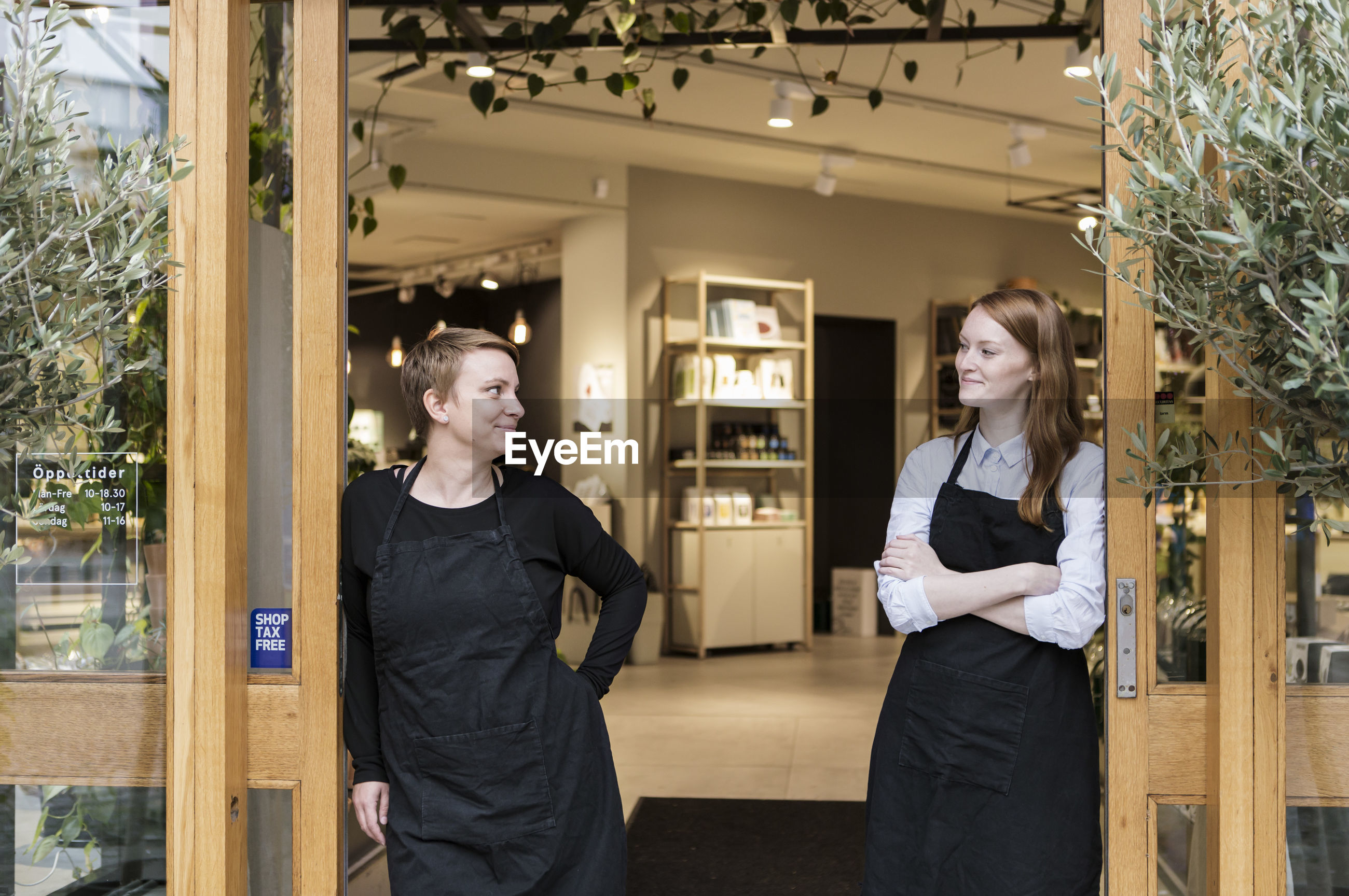 Smiling female owners standing at doorway of store