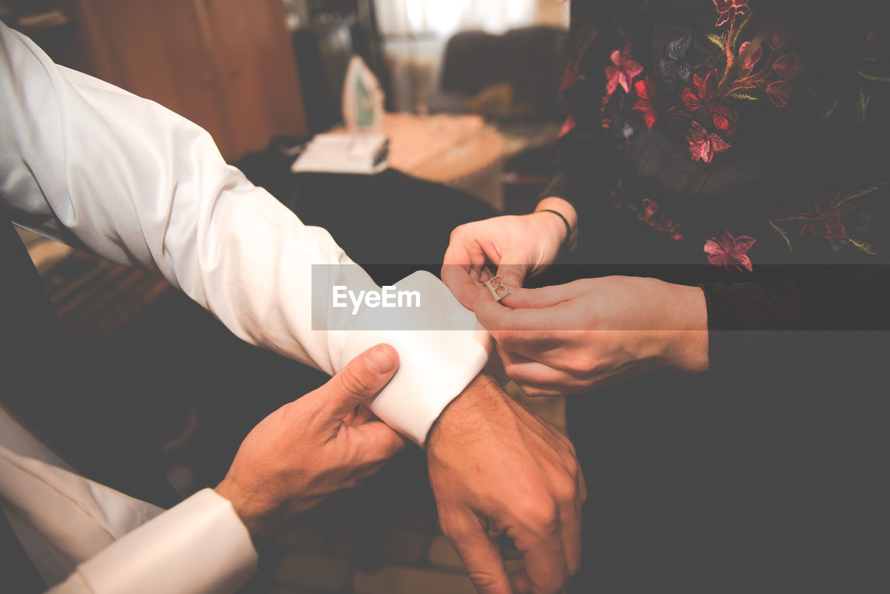 Bride Attaching Cuff Link On Bridegroom Sleeve During Wedding