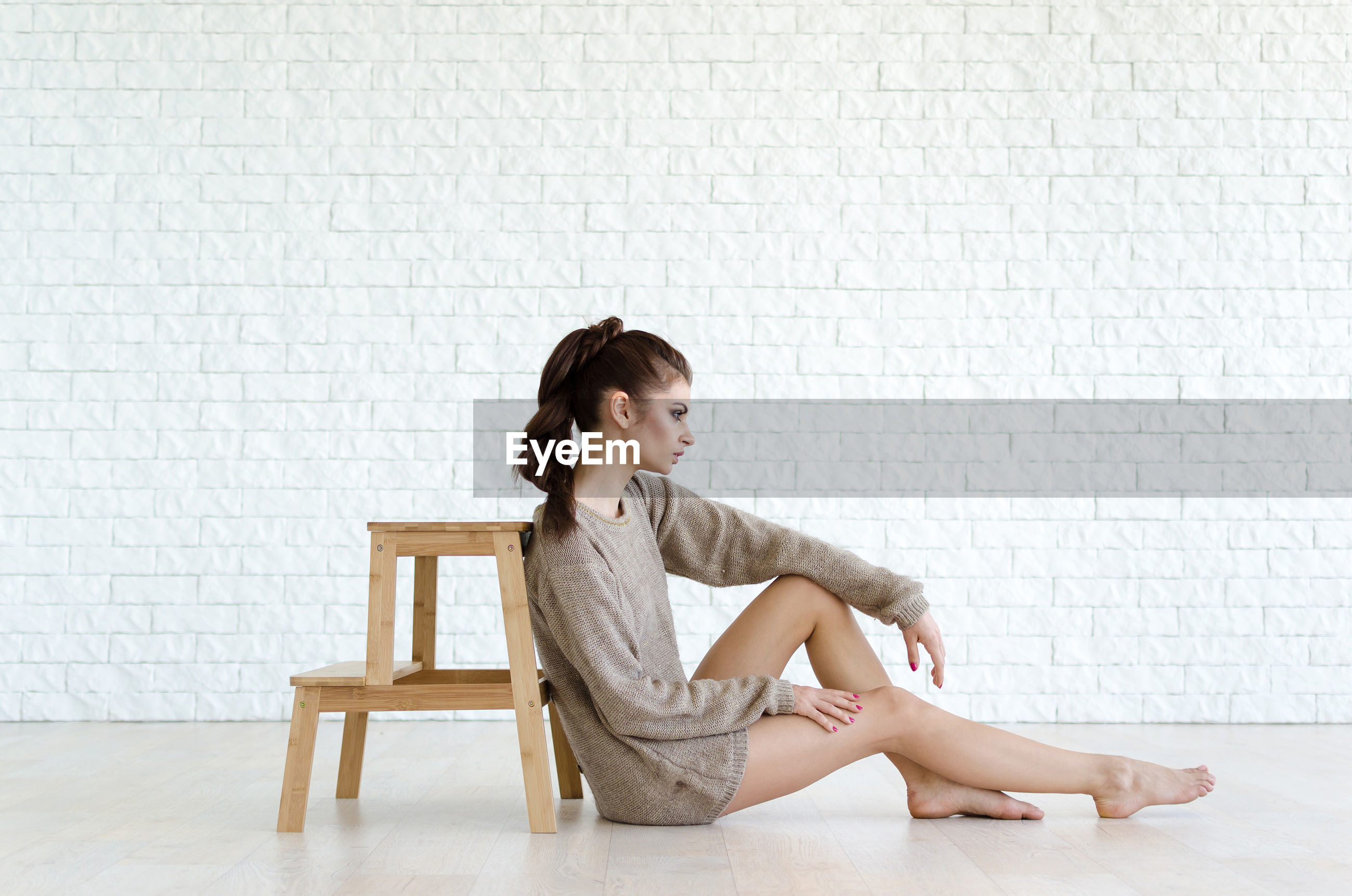 Full length of young woman sitting by wood stool against brick wall