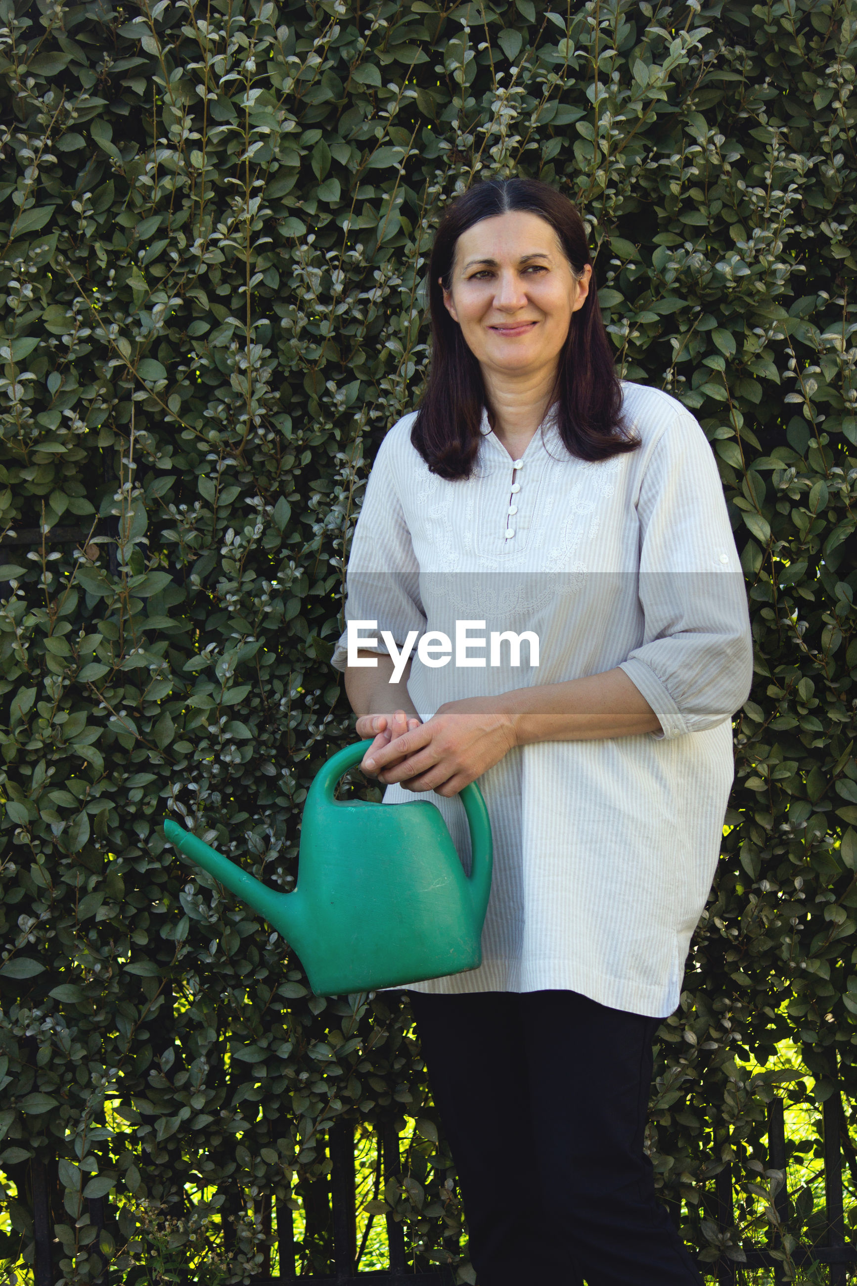 Smiling woman holding watering can while standing against plants