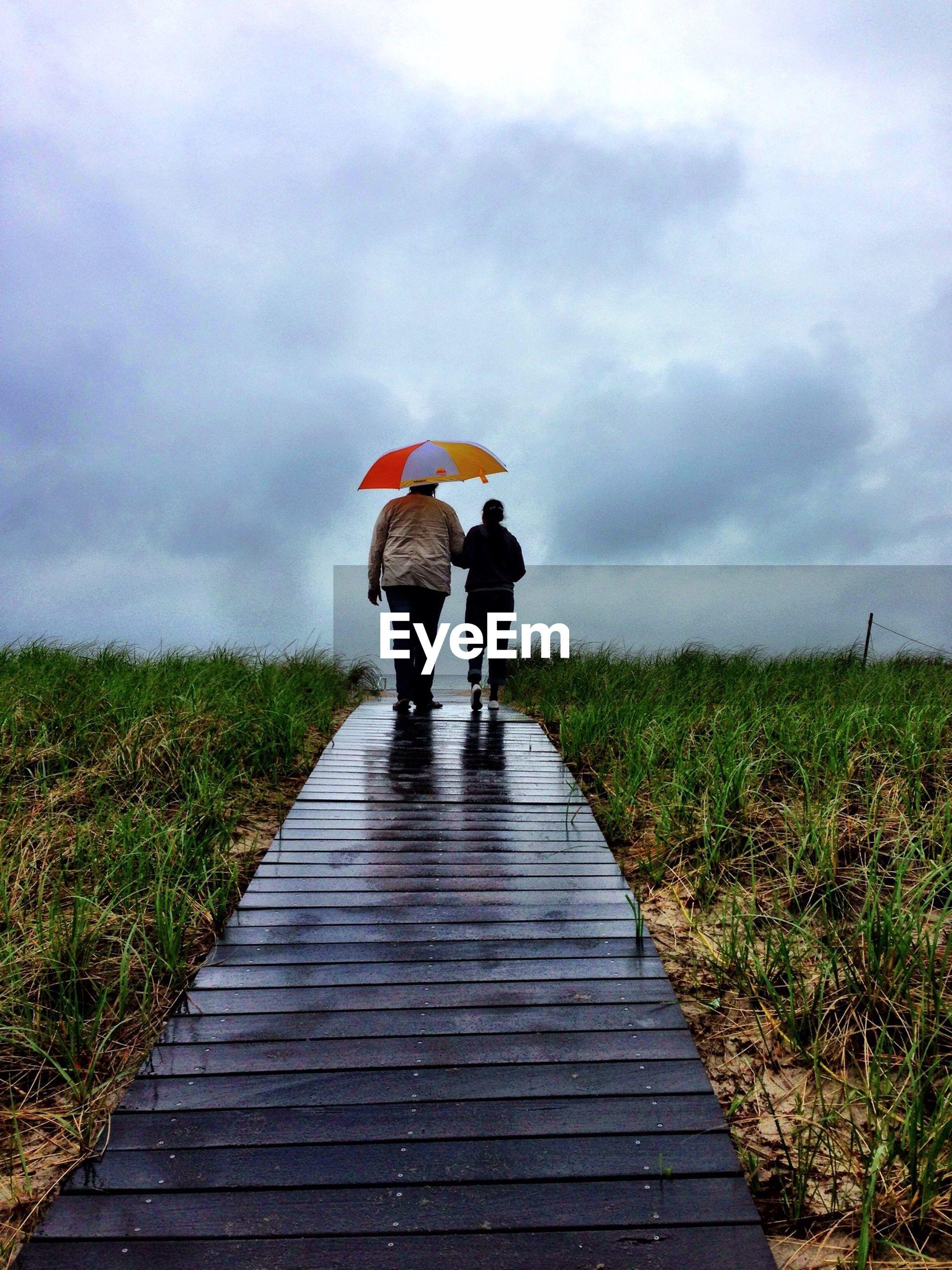 Rear view of couple walking on boardwalk