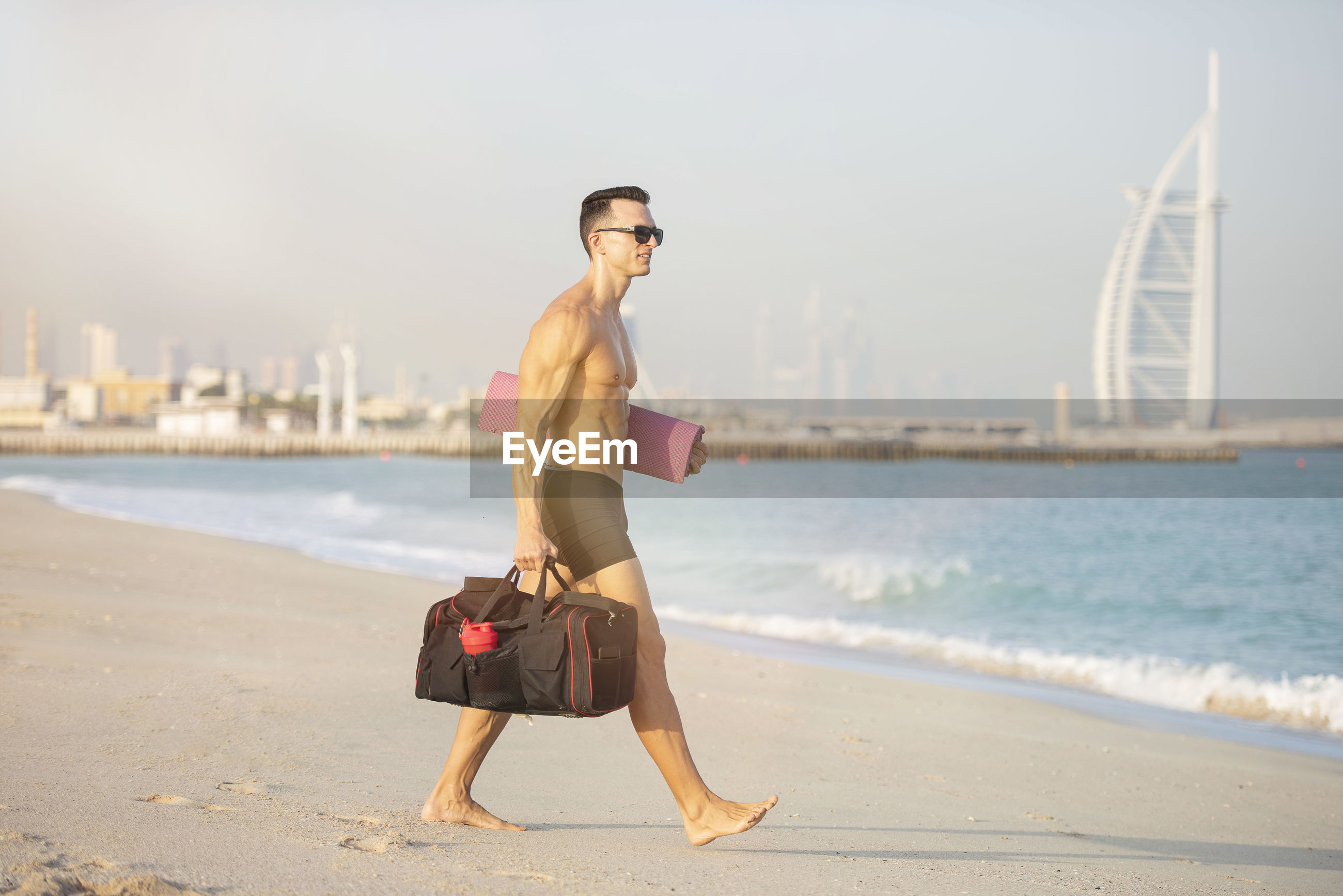 Full length of shirtless man walking while holding bag at beach