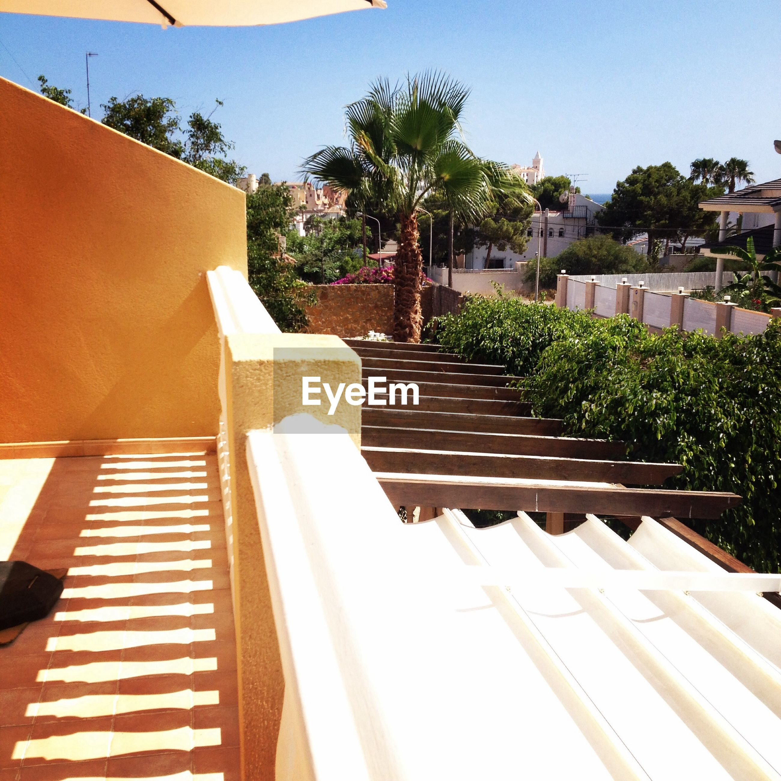 building exterior, architecture, built structure, low angle view, roof, tree, clear sky, sunlight, house, steps, sky, railing, steps and staircases, no people, day, residential building, residential structure, building, shadow, outdoors
