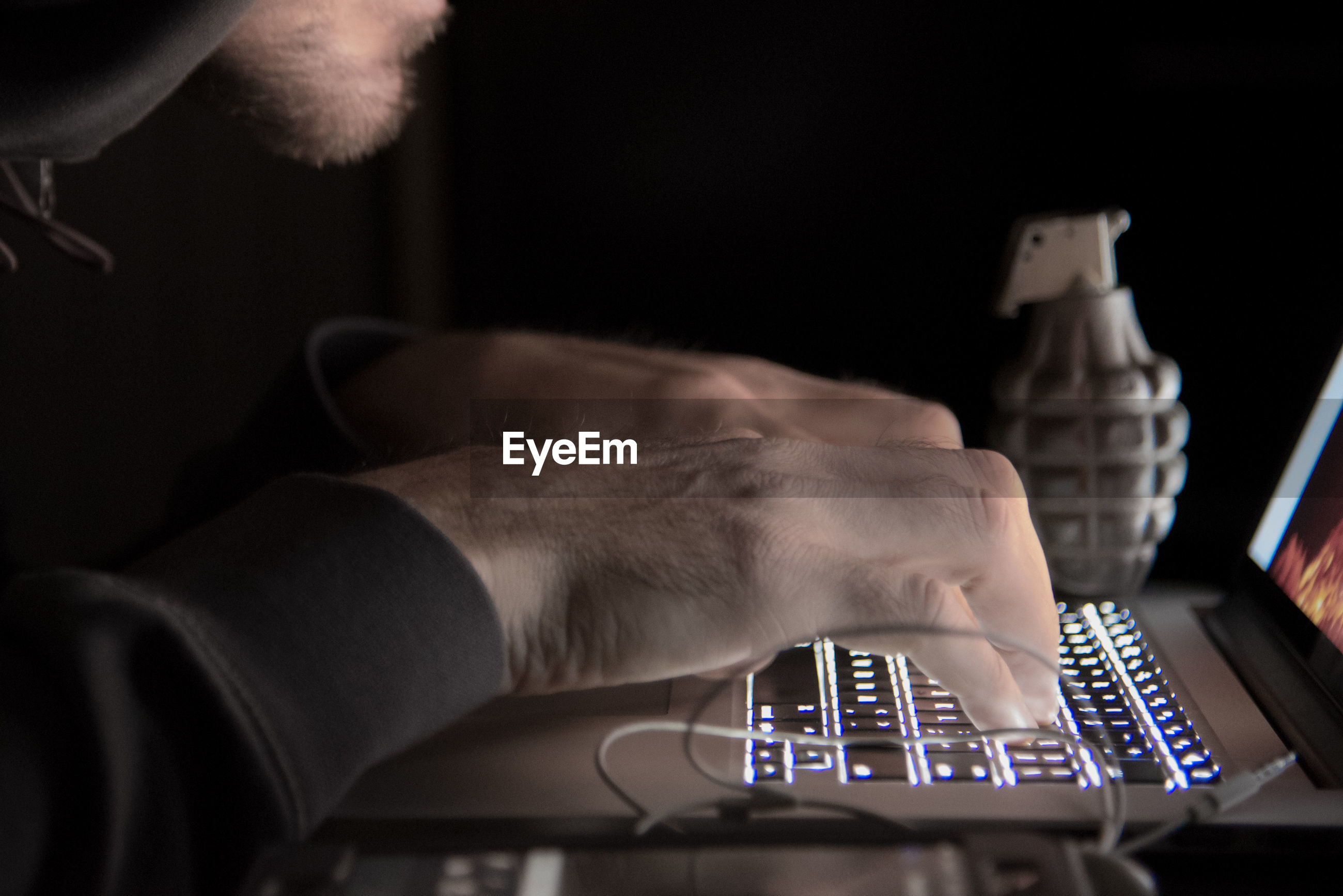 Midsection of computer hacker using laptop in darkroom