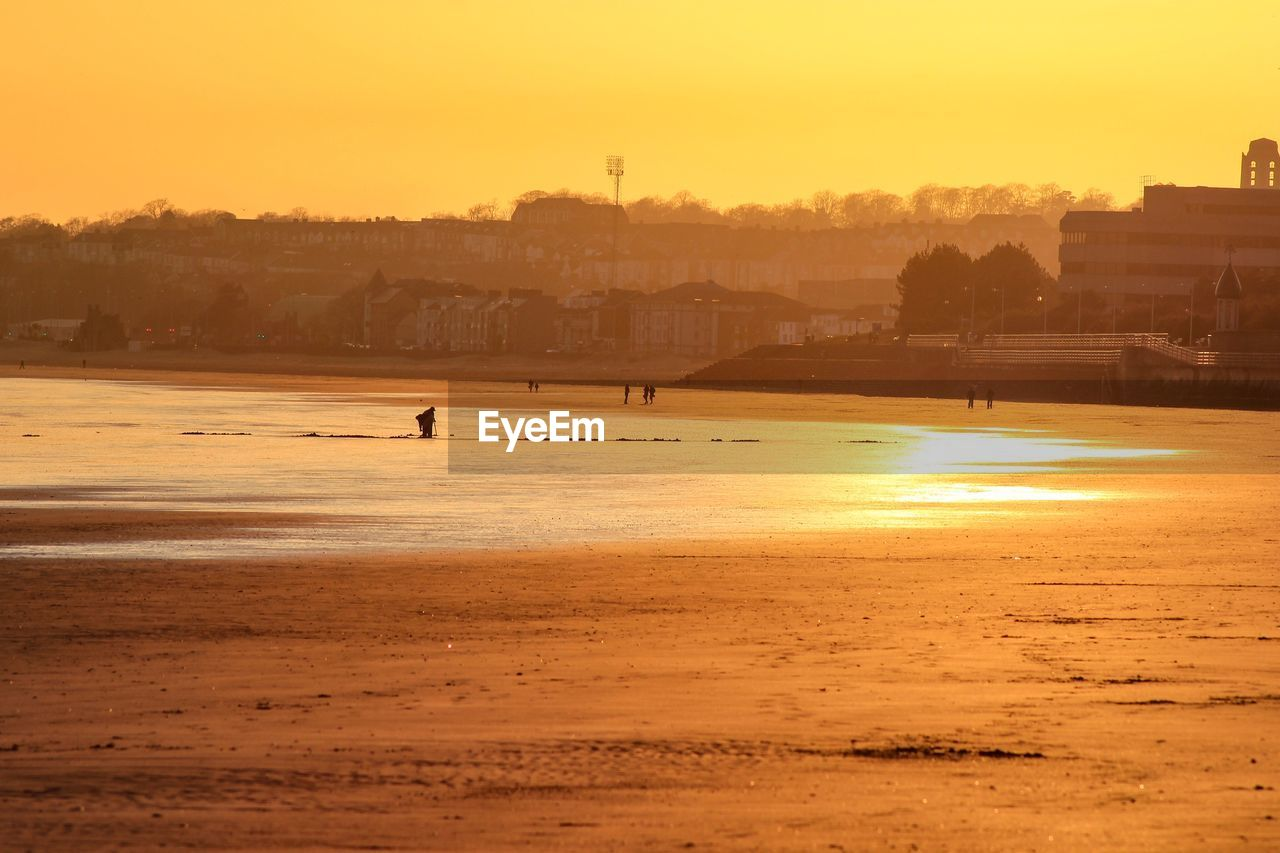 water, sky, sunset, building exterior, built structure, architecture, nature, beach, land, scenics - nature, silhouette, sea, beauty in nature, orange color, tranquil scene, outdoors, tranquility, sand, no people
