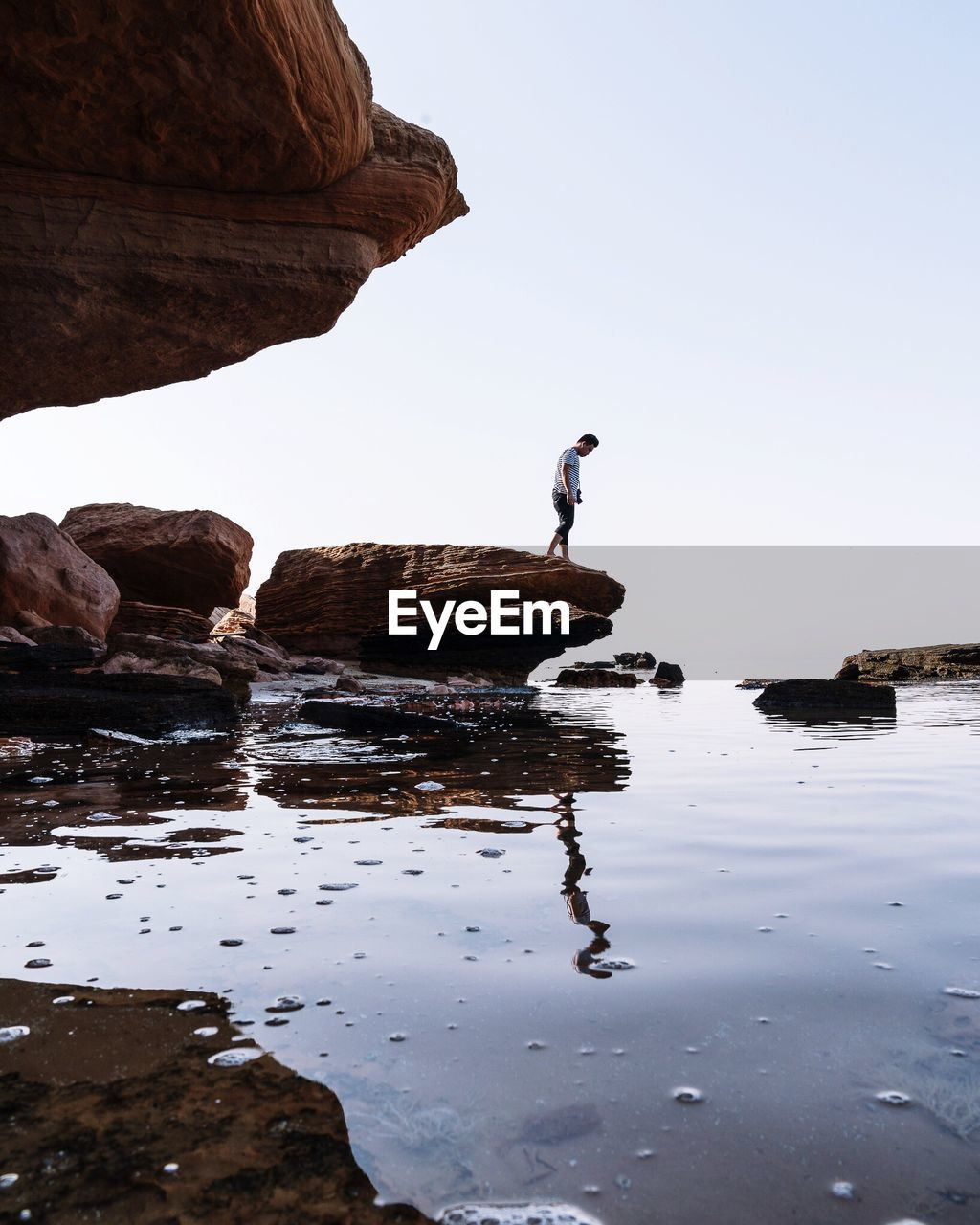 Man standing on rock formation at beach against sky