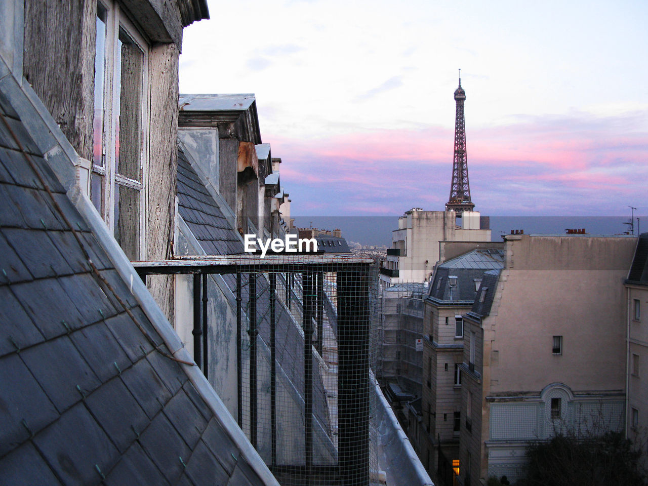 Distant View Of Eiffel Tower Amidst Buildings In City At Dusk
