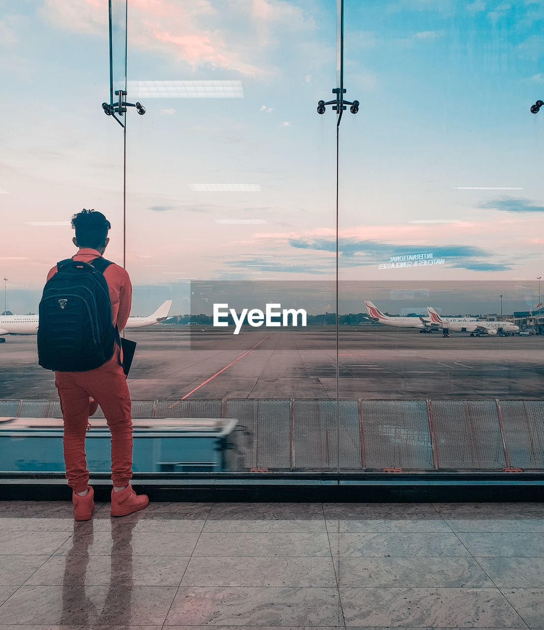 sky, rear view, airport, transportation, airplane, air vehicle, one person, cloud - sky, full length, standing, glass - material, real people, airport runway, sunset, travel, mode of transportation, men, nature, transparent, outdoors, looking at view, waiting
