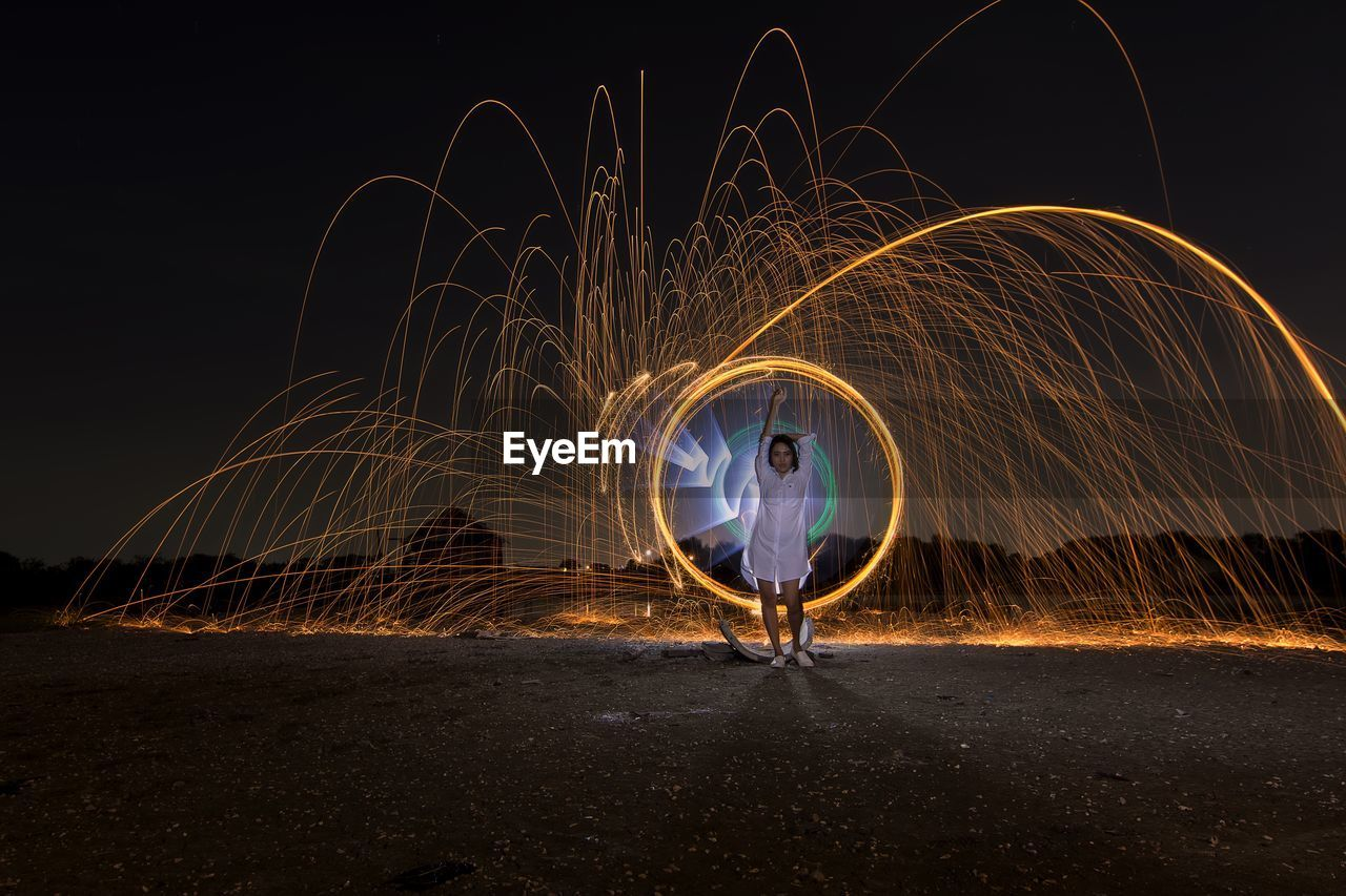 Full Length Of Woman With Wire Wool Against Sky At Night